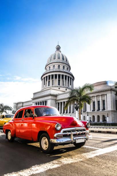 Red Vintage Car In Front El Capitolio Building In Havana, Cuba stock photo