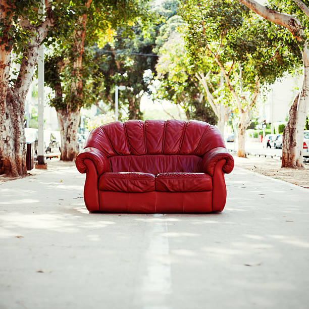 red vintage leather sofa on the street stock photo