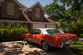 Horizontal view of a white and red vintage Oldsmobile parked at the entrance gate of an exclusive detached residential house in Suffolk Dr, Afton Oaks, Houston, Texas