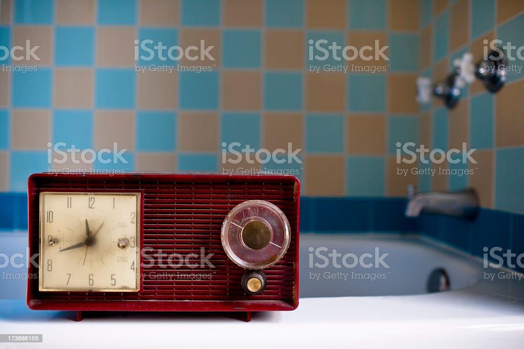 red vintage retro radio sitting on bath tub ledge stock photo