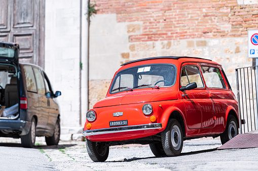 Montepulciano, Italy - August 28, 2018: Red chrome vintage retro style Autobianchi small Italian car produced by Pirelli, Fiat and Bianchi parked on street of Italian small town or city