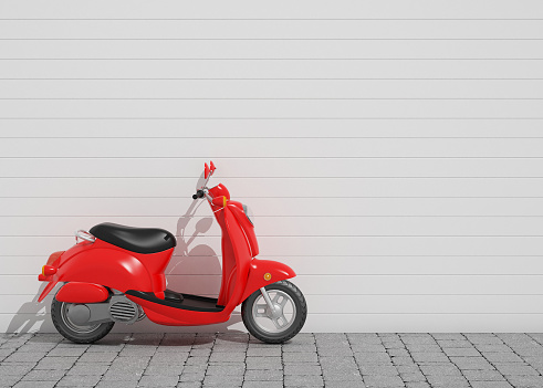 A red vintage scooter leaning on a white wall