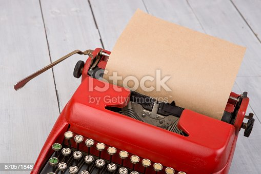 Red vintage typewriter with blank paper sheet on white wooden table