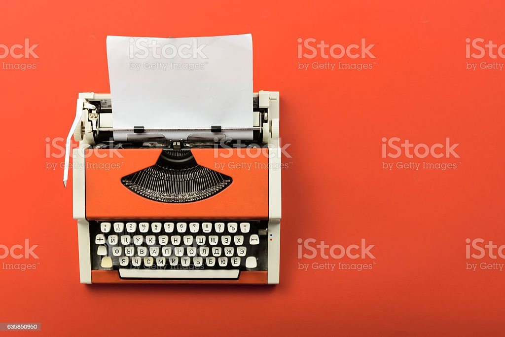 Red vintage typewriter with white blank paper sheet stock photo
