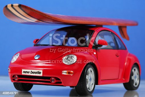 Cantley, Quebec, Canada - February 20, 2009: Red Toy car Volkswagen New Beetle with wood surfboard on car roof with a blue background. This Red Volkswagen New Beetle is the Special Edition 1:25 product by Maisto. Maisto was founded in 1967 and is a company that manufactures die-cast models of aircraft, motorcycles and automobiles. The small wooden surfboard decoration have no brand-name on it.