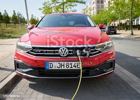 Duesseldorf, Germany- July 22. 2020: A red Volkswagen Passat is parked in the city of Duesseldorf and is connected with a yellow power chord to a recharging station.
