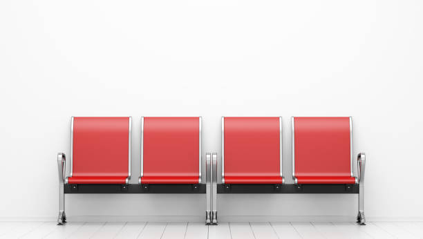 red waiting chairs in front of white wall stock photo