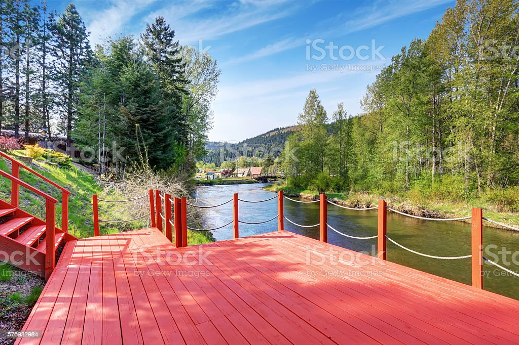 Red walkout deck with staircase on river bank stock photo