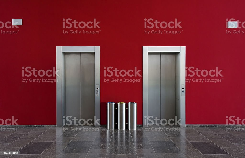 Red wall and two elevator doors royalty-free stock photo