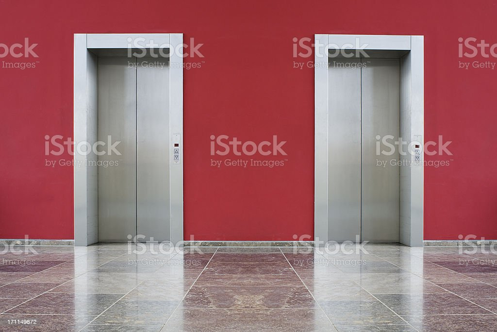 Red wall, two elevator doors stock photo