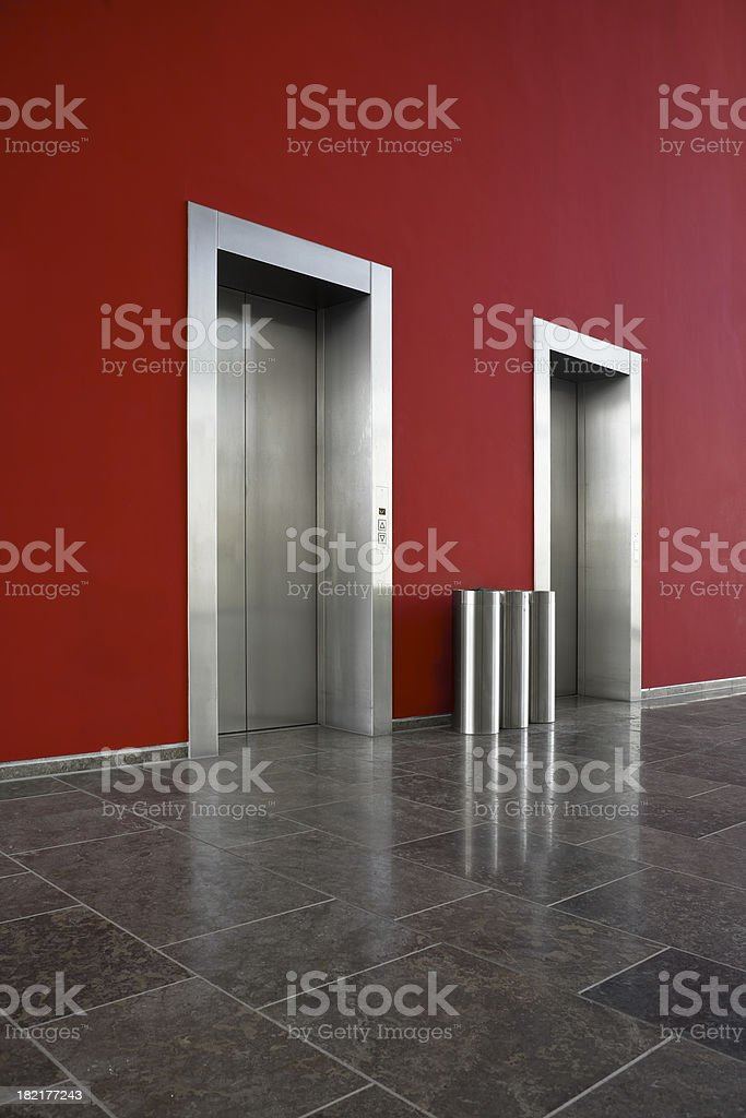Red wall, two elevator doors, waste bins royalty-free stock photo