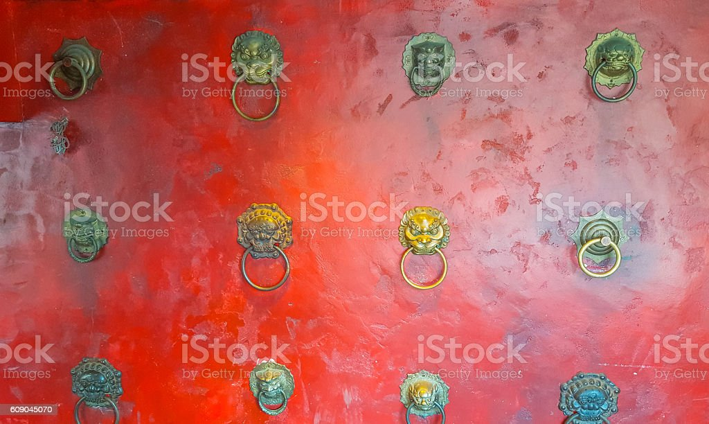 Red wall with door knockers stock photo