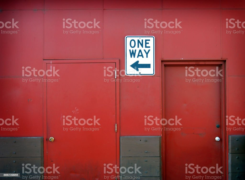 red wall with one way sign stock photo
