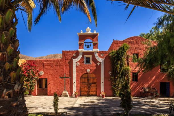 Rote Wände der spanischen katholischen Kapelle mit Palmen, Bäumen und Blumen, Arequipa, Peru – Foto