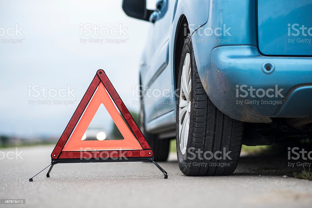 Red warning triangle next to broken car stock photo