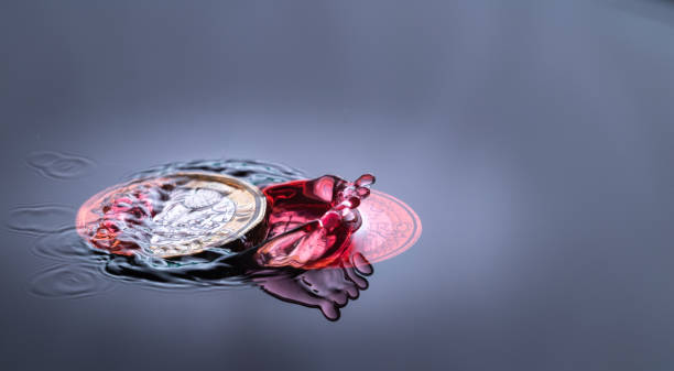 red water drop splash on a coin red colored water drop splashing on a Euro and english pond sterling coin depreciation stock pictures, royalty-free photos & images