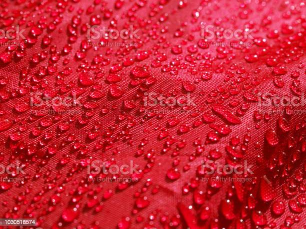 Photo of Red waterproof fabric with waterdrops close up