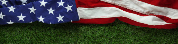 Red, white, and blue American flag on grass for Memorial Day or Veteran's day background stock photo
