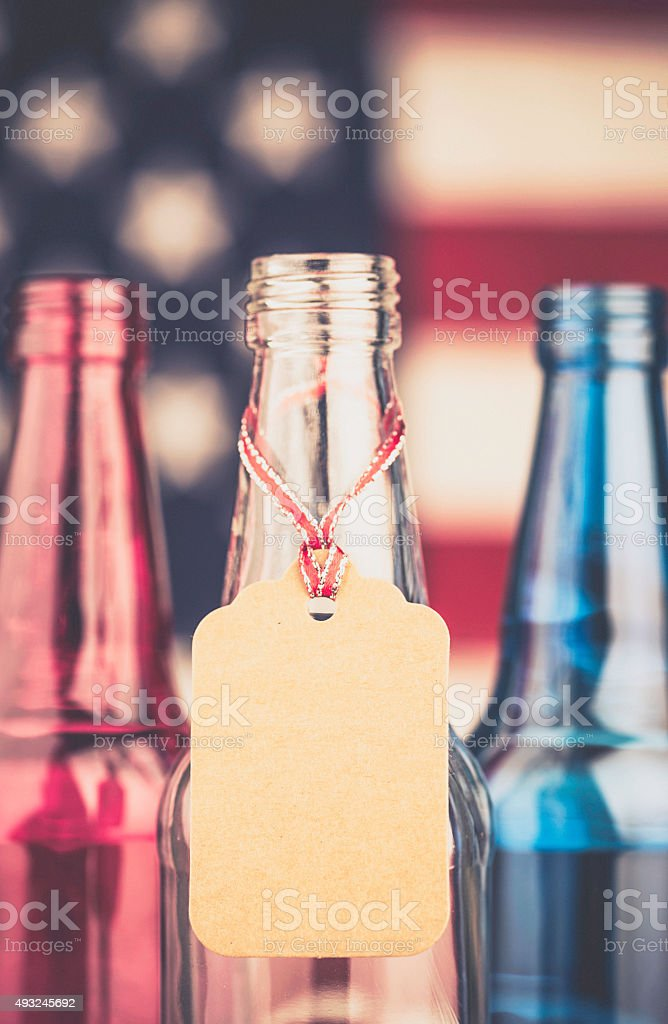 Red, white and blue beer bottles with blank gift tag stock photo
