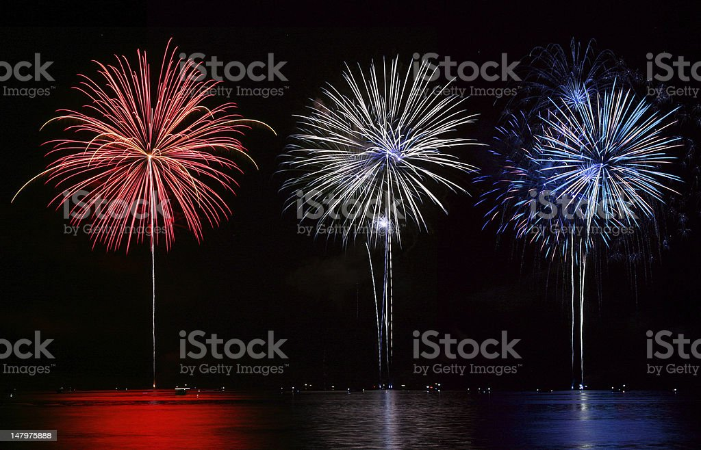 Red, white and blue fireworks set off over lake stock photo