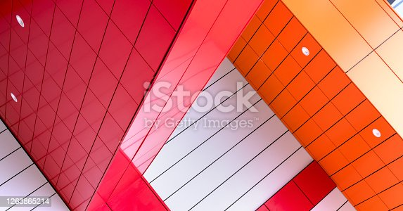 red white and orange construction represents fashionable architecture in city centre under bright summer sunlight
