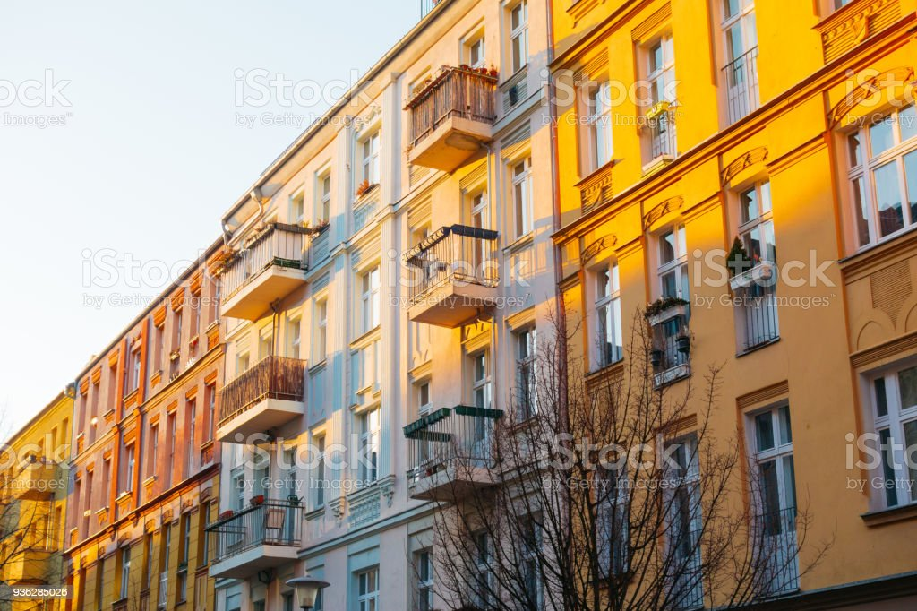 red, white and orange houses in a row for real estate themes stock photo