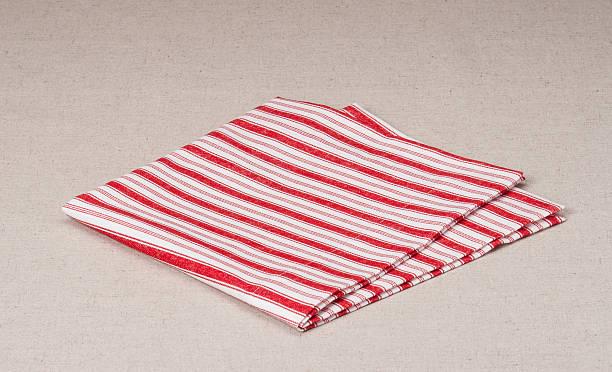 красный белый сложенный салфетка на натурального льна фоне - rbg стоковые фото и изображения