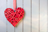 Red wicker heart on a wooden painted background