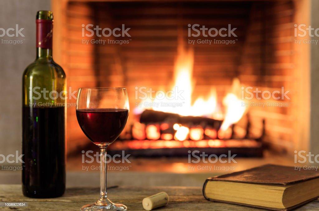 Vin rouge et un fond de cheminée de livre - Photo
