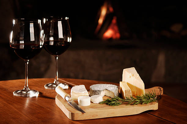 red wine and cheese at fireplace stock photo