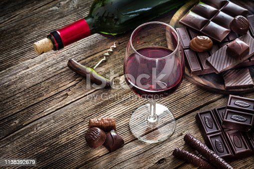High angle view of a red wineglass and a selection of various chocolate bars, truffles and pralines shot on rustic wooden table. A wine bottle is at background and complete the composition. Copy space available for text and/or logo. Predominant color is brown. Low key DSRL studio photo taken with Canon EOS 5D Mk II and Canon EF 100mm f/2.8L Macro IS USM.