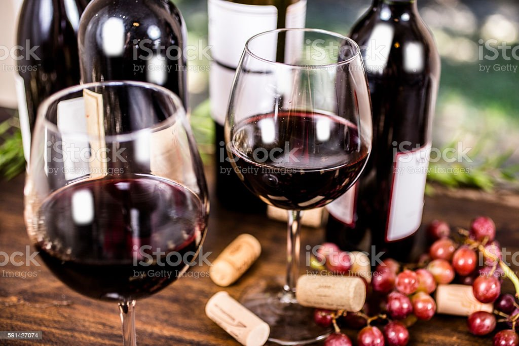 Red wine and grapes on outdoor dining table. stock photo