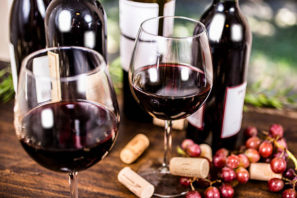 Red wine and grapes on outdoor dining table. Wine tasting event. Red wine selections on outdoor patio table.  Wine bottles in background. Rustic wooden table with grapes.  No people. red wine stock pictures, royalty-free photos & images