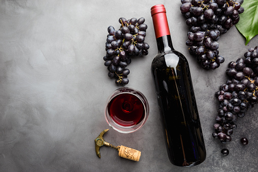 Red wine in a glass and ripe grapes on gray background, top view
