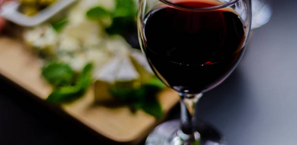 Vinho vermelho e jogo de queijos diferentes em uma placa de madeira, petisco delicioso - foto de acervo