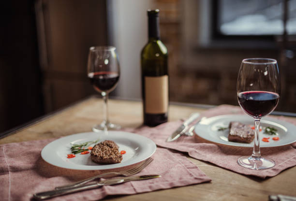 Red wine and steaks Red wine in glasses with wine bottle and delicious steaks on plates table for two stock pictures, royalty-free photos & images