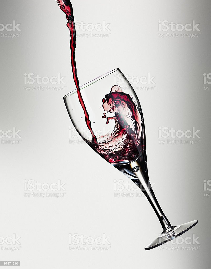 Red wine being poured into floating glass royalty-free stock photo