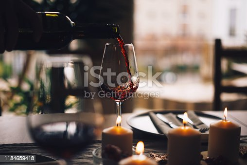 Red wine being poured into the glass at the table