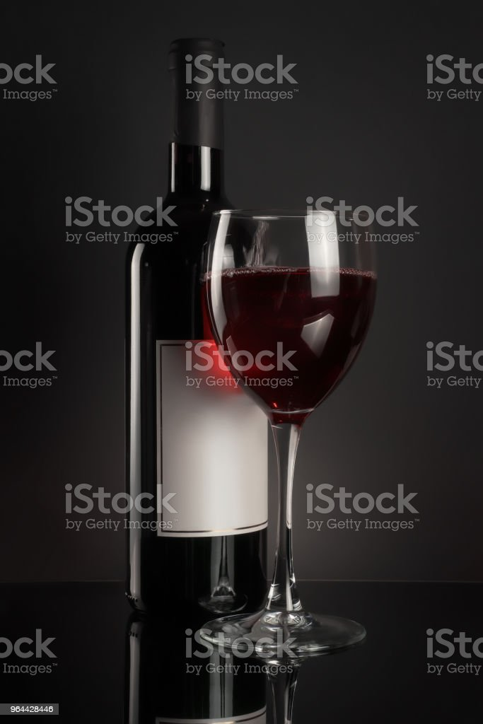 Red wine bottle and full wineglass on black - Royalty-free Alcohol Stock Photo