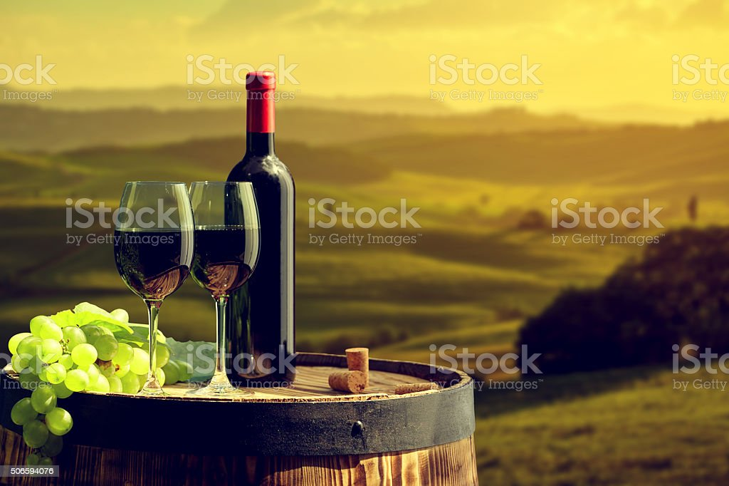 Red wine bottle and  glass on old barrel. stock photo
