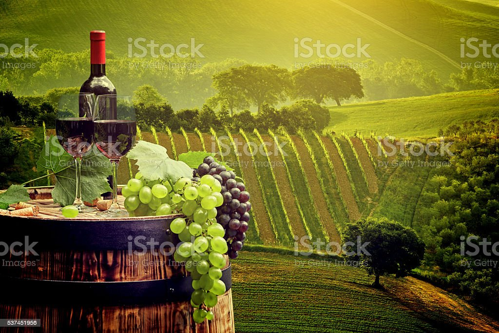Red wine bottle and glass on wodden barrel. stock photo