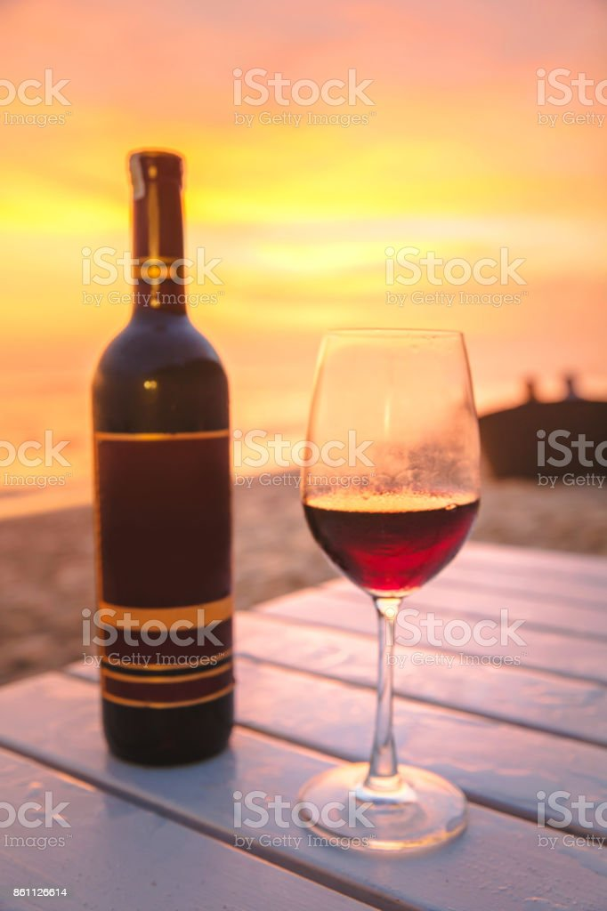 Red wine bottle & glass with sunset background - foto stock