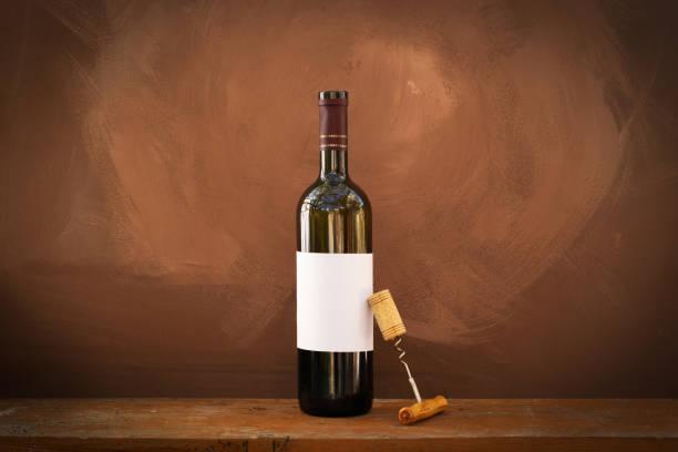 flasche rotwein auf einem hölzernen hintergrund - mini weinflaschen stock-fotos und bilder
