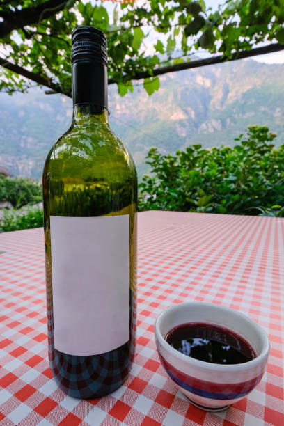 Red wine bottle with blank label and famous ceramic boccalino mug in a rock grotto restaurant, Ticino, Switzerland stock photo