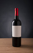 red wine bottle with blank label for any brand on the table aginst black background