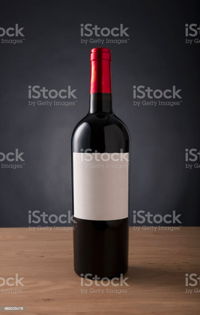 red wine bottle with blank label for any brand on the table aginst black background stock photo