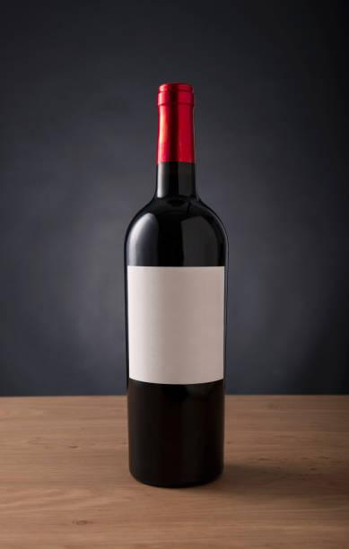 Flasche Rotwein mit leere Beschriftung für jede Marke auf dem Tisch Aginst schwarzen Hintergrund – Foto