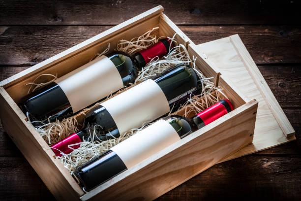rött vin flaskor förpackade i en trälåda som sköt rustika träbord - wine box bildbanksfoton och bilder