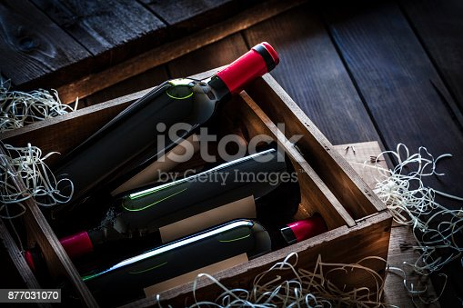 High angle view of a wooden box with three red wine bottles shot on rustic wooden table. The labels on the bottles are blank so you can put any design on them. Predominant color is brown.