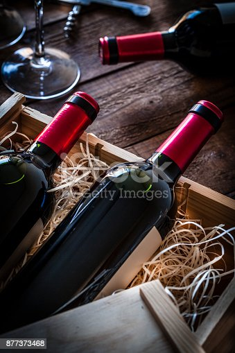 High angle view of a wooden box with two red wine bottles inside it and a third bottle out the box. At the top-left corner is visible a wine glass and a corkscrew. Predominant colors are brown and red. Low key DSRL studio photo taken with Canon EOS 5D Mk II and Canon EF 100mm f/2.8L Macro IS USM
